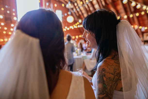 Two brides seated at wedding wearing matching veils