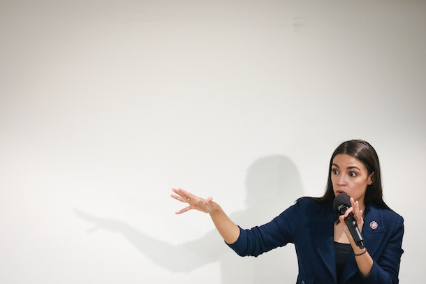 Alexandria Ocasio-Cortez , who is known for her inspiring quotes on female empowerment, speaks into a microphone.