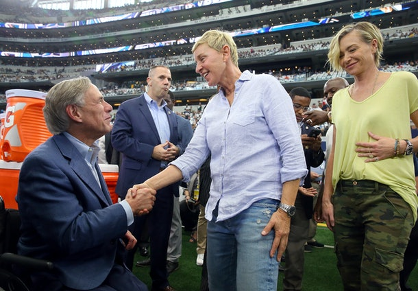 Ellen Degeneres and wife Portia DeRossi shake hands with an official at an NFL game