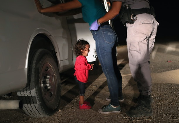 A picture of a young immigrant child, crying, while her parent is being searched by a border patrol agent.
