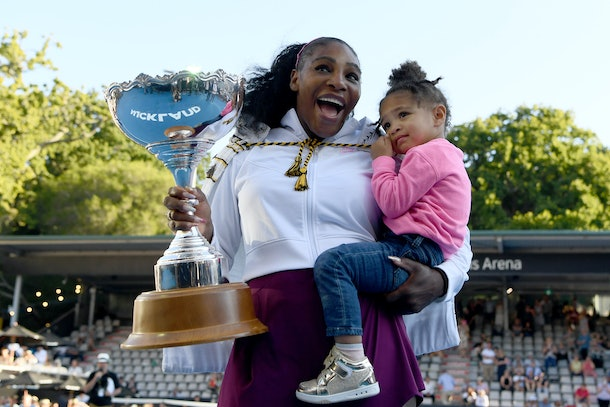Serena Williams celebrates winning her first title since giving birth with daughter Olympia.