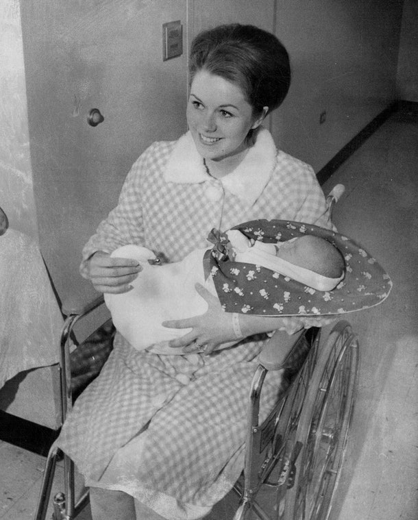 This mom wheels her baby home from the maternity ward in a snowman blanket on Christmas Day 1968.
