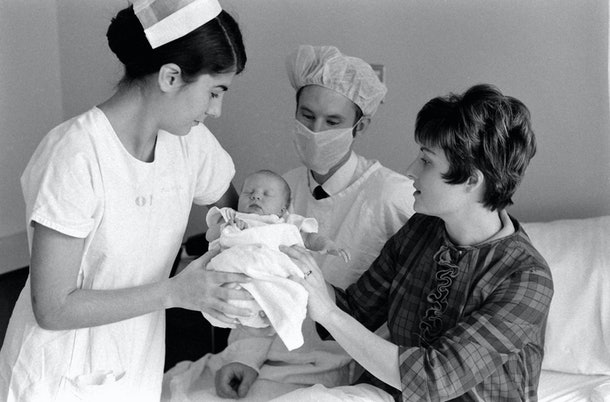 A proud 1969 mom passes her newborn to a nurse and doctor.