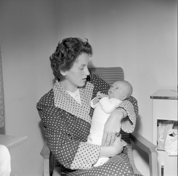 This 1957 mom in her polka dot robe looks like she's getting a real good look at her brand new baby in the hospital.
