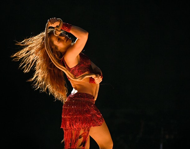 Shakira performs at the Super Bowl halftime show in a red fringe outfit, holding a rope