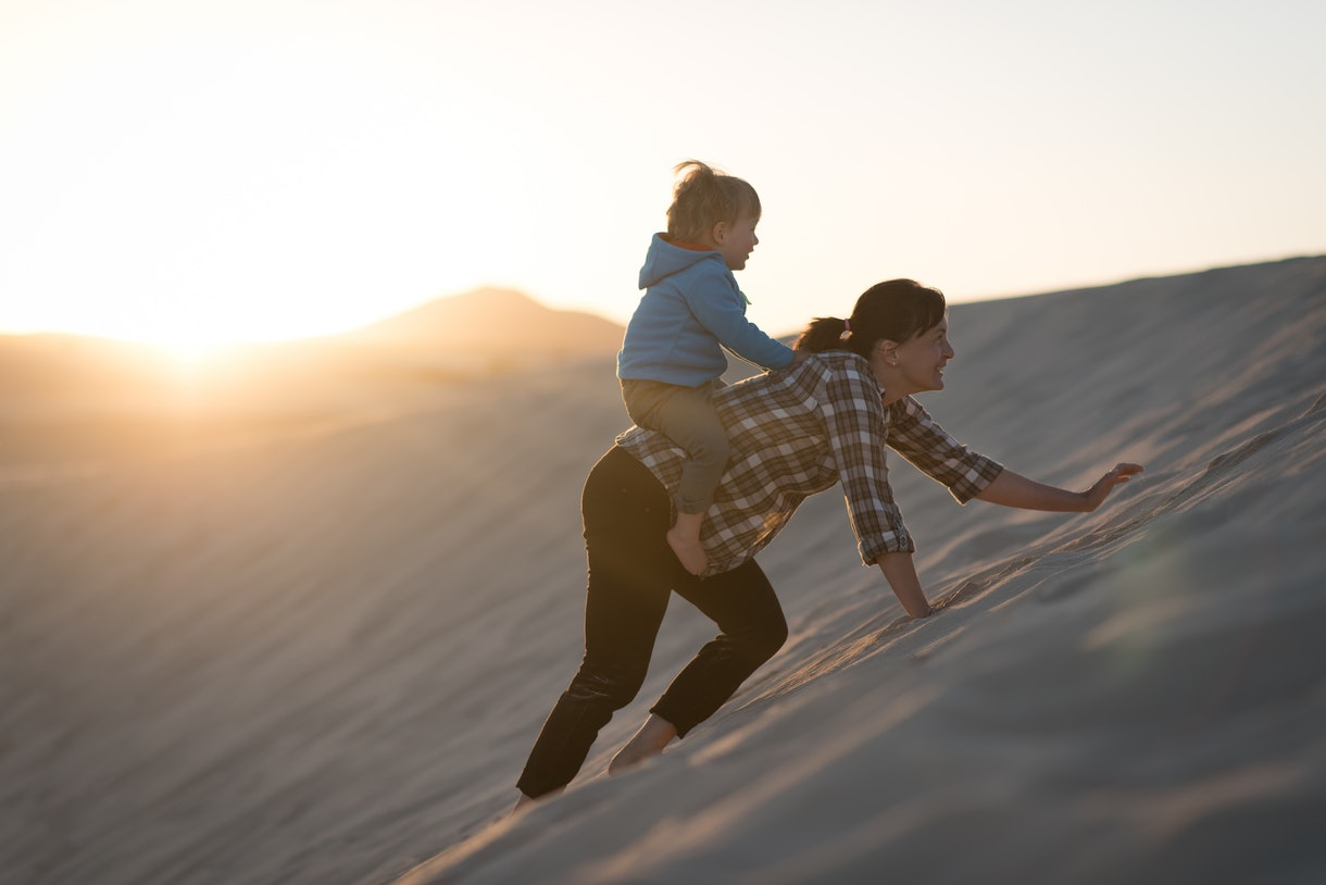 A mom carries her baby on her back in a sand dune.