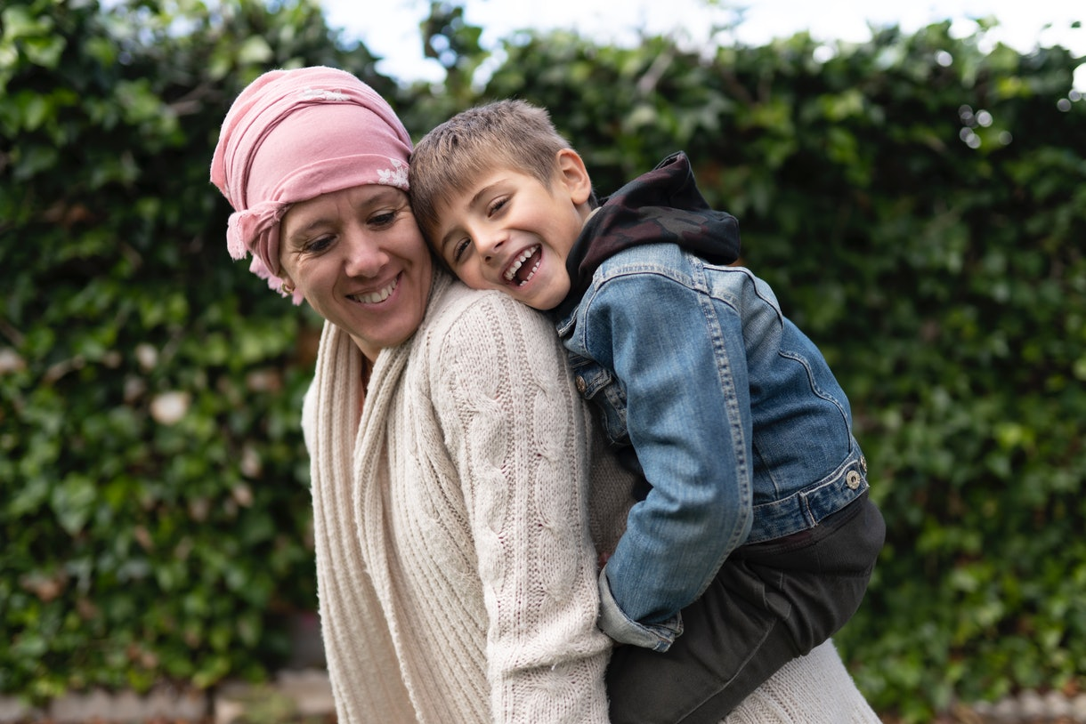 A mother going through cancer treatments laughs with her son.