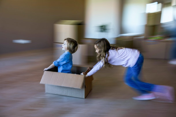 Playing with a cardboard box is a summer activity kids can do at home.