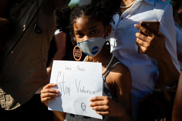 A young girl in a mask calls for a stop to violence