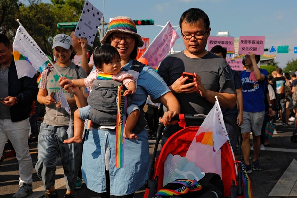 A family marches together at a Pride celebration