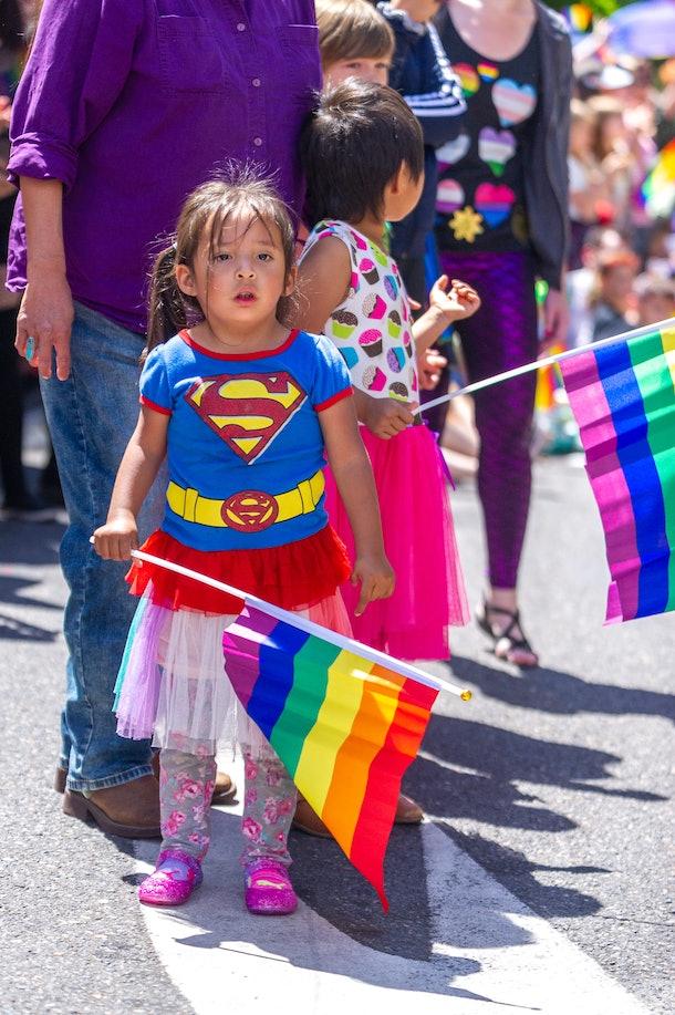 A young girl holds a rainbow flag
