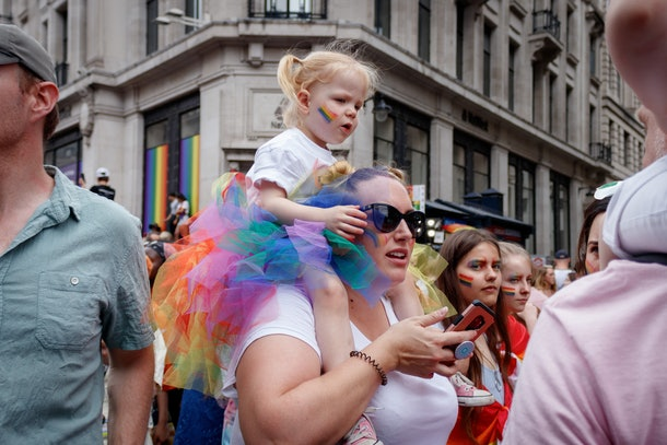 A girl rides on a woman's shoulders at a Pride celebration