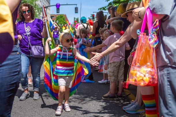 Children high five at a Pride event