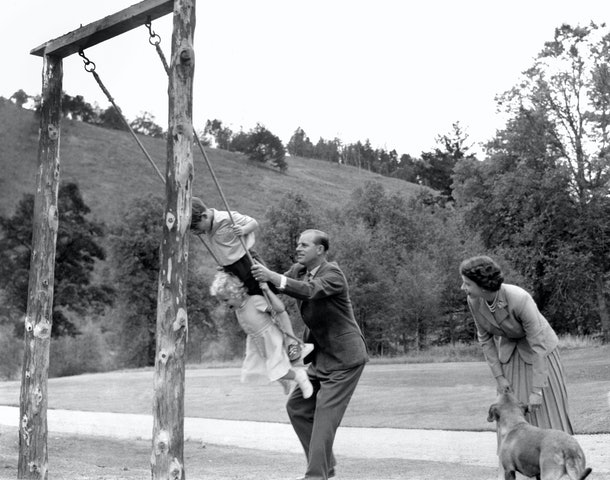 Prince Philip pushes Prince Charles and Princess Anne on a swing in 1955.