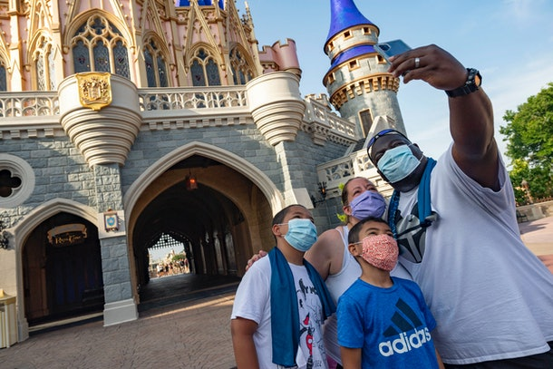 Family poses for a selfie outside Cinderella's Castle in the Magic Kingdom.