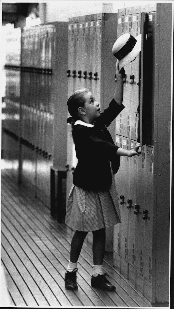 This vintage back to school photo shows a little girl attempting to put her hat in her locker.