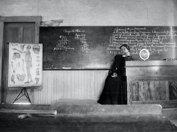 This vintage back to school photo shows a teacher in front of her chalkboard.
