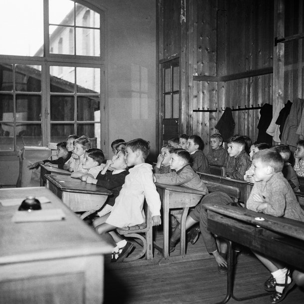 This vintage back to school photo shows a variety of students learning in their classroom.