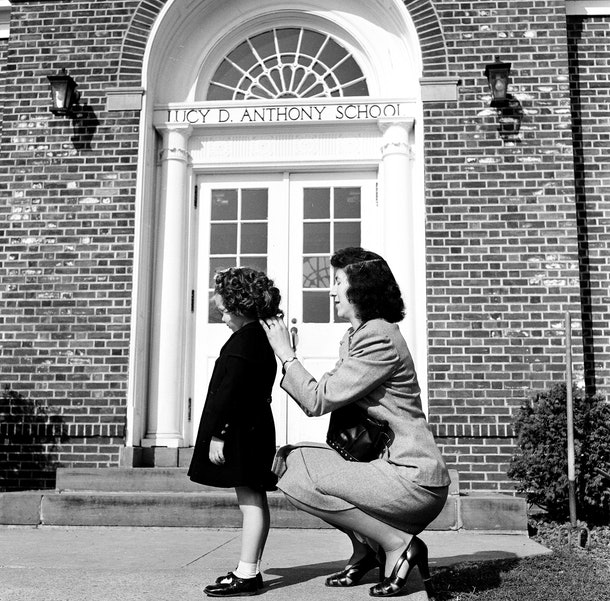 This vintage back to school photo shows a mom putting the finishing touches on her child's first day look.
