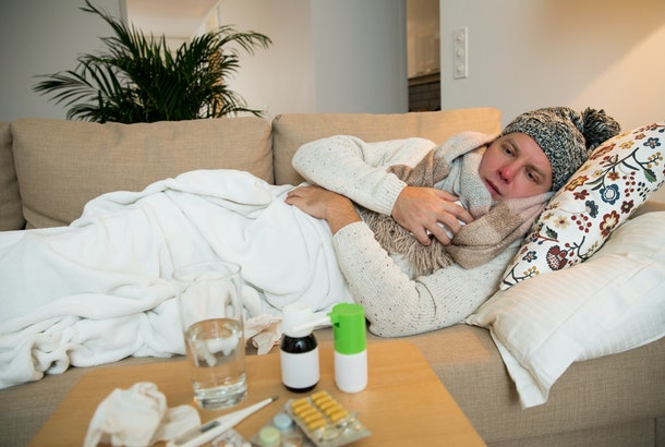 man huddles on couch in beanie, blanket, and scarf