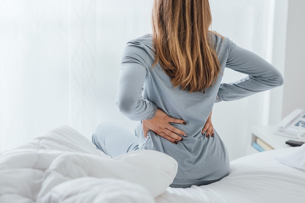 woman sitting on edge of bed grabbing her back with both hands in pain