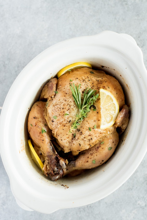 whole chicken garnished with a sprig of rosemary and  lemon in a white pot