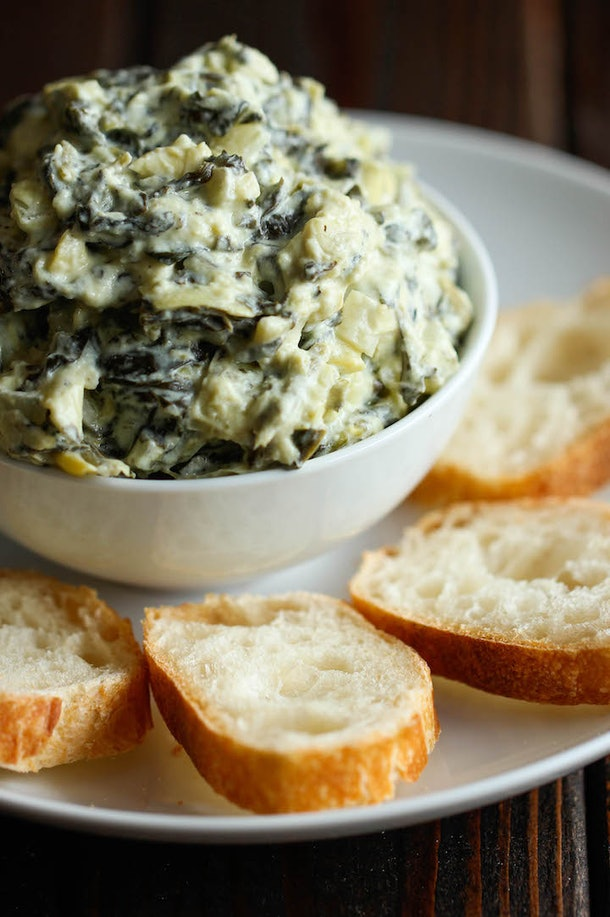 close up of bowl of artichoke dip with sliced baguette on the side