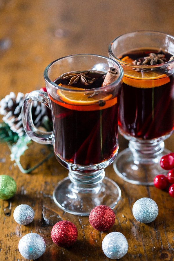 two glasses of mulled wine with cinnamon sticks and oranges inside