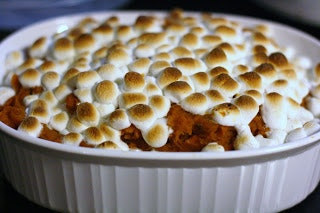 white porcelain bowl full of sweet potatoes with burnt marshmallows on top