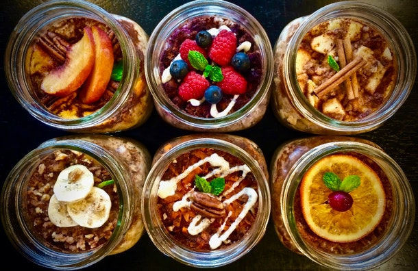 aerial view of an assortment of 6 jars with oatmeal garnished with different fruits or nuts