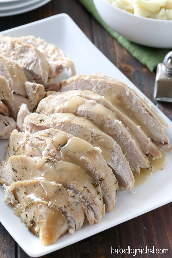 sliced turkey with gravy layered on top presented in a white square dish on a wooden table
