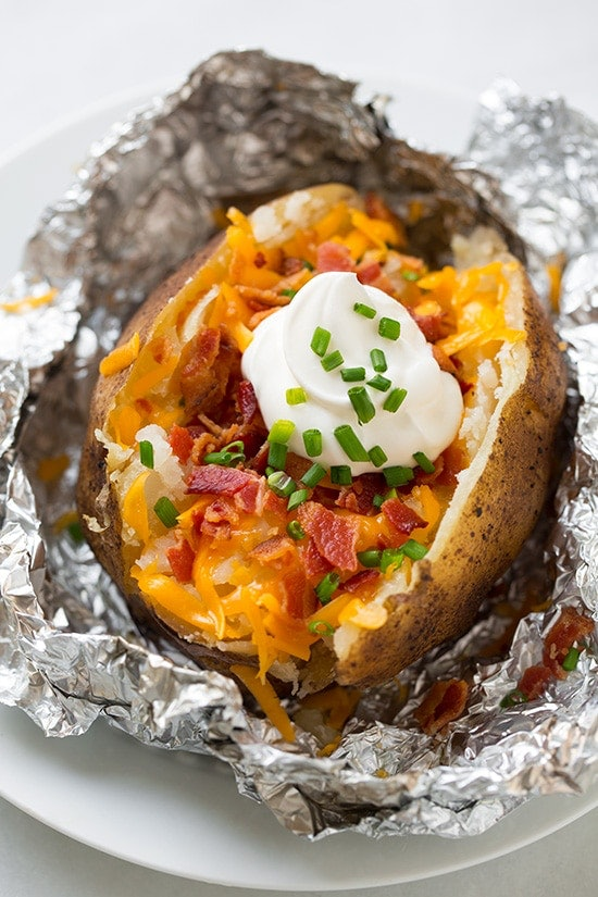 baked potato with shredded cheddar cheese, bacon, chives and sour cream presented in tinfoil on a plate