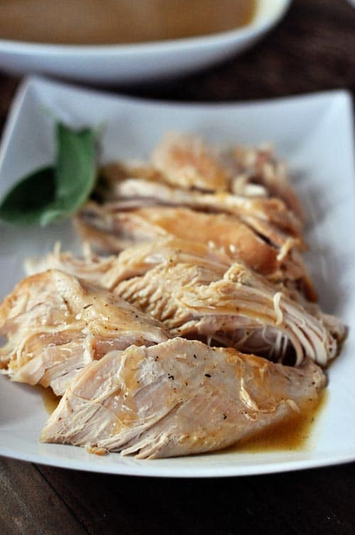 close up of cut up turkey with gravy drizzled over on a plate with a green leaf garnish on the side