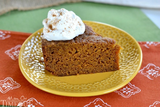 slice of pumpkin bread on a yellow plate topped with whipped cream and cinnamon powder
