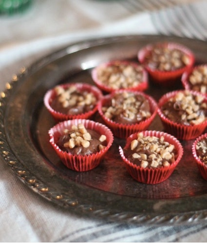 silver tray with small red cups of chocolate and nuts inside