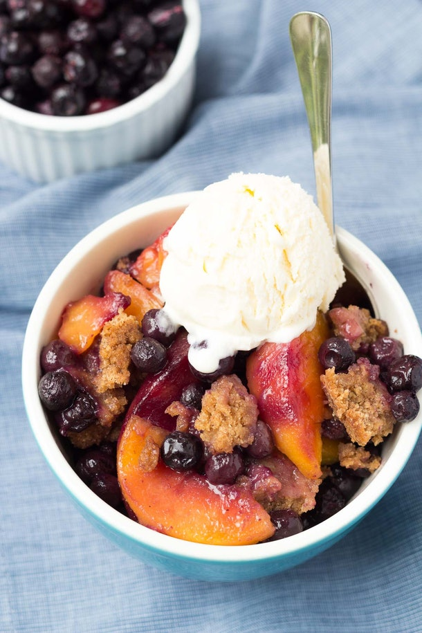 blueberries and peaches in a bowl with a crumble topped with ice cream
