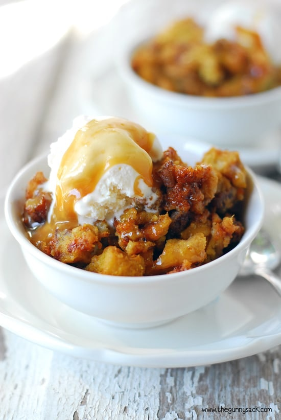 two bowls of pumpkin pecan bread pudding topped with ice cream and caramel drizzle