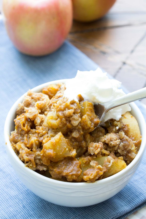 apple pie filling mixed with a crumble in a bowl with whipped cream on top
