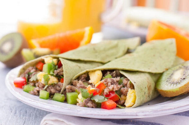 two burritos full of red and green peppers, chopped meat and eggs on a plate next to sliced kiwi and oranges in the background