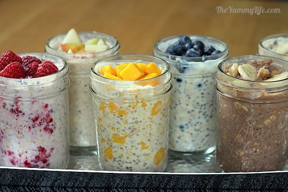 metal tray full of clear jars of overnight oats in yogurt with different fruits in each jar