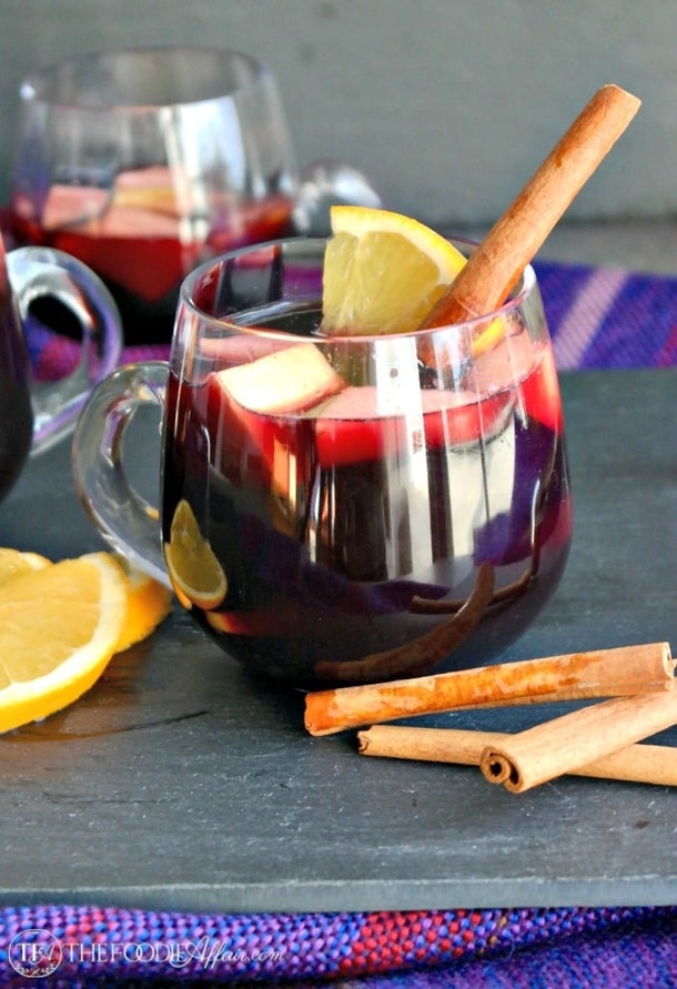 glass mug of sangria with a cinnamon stick, sliced oranges and apples inside