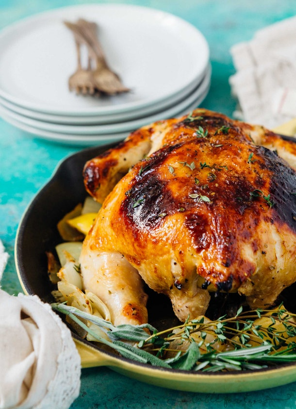 whole roasted chicken with rosemary in a pan being served on a table