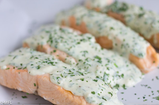 cooked salmon with a creamy cheese sauce on top