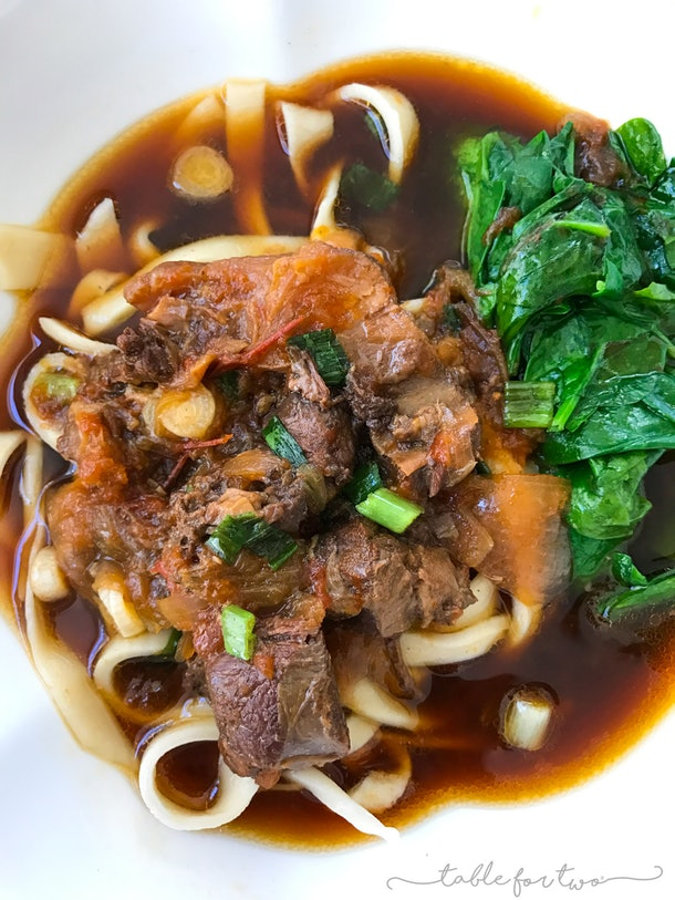 beef and noodles in a stew with spinach