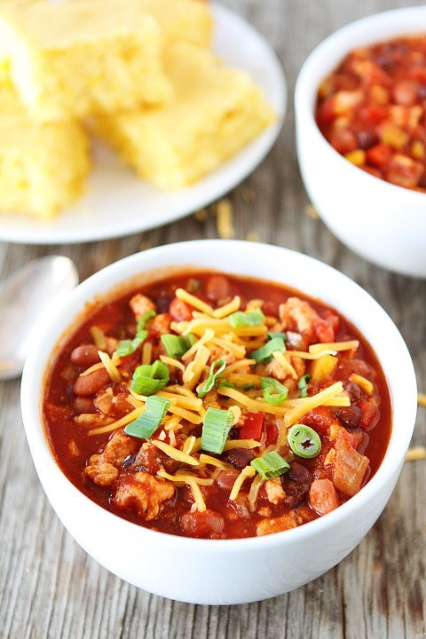 white bowl full of red soup with shredded cheese on top