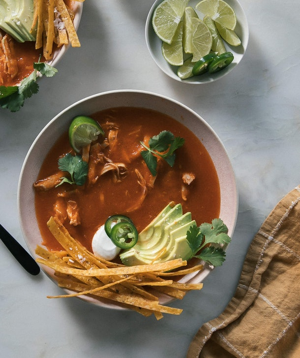 bowl of red soup garnished with sliced avocado, tortilla chips, cilantro, jalapeno peppers, and lime  next to a brown cloth on a  white, marble table.