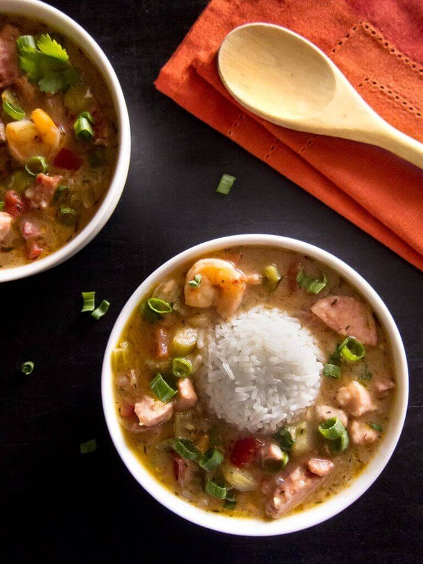combination of brown soup with white rice, an assortment of vegetables shrimp and meat