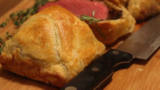 close up of beef wellington next to knife