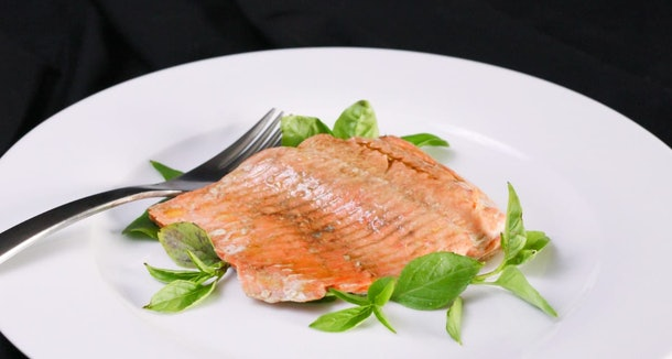 cooked salmon with green garnish on a white plate with a silver fork to the left of the salmon.