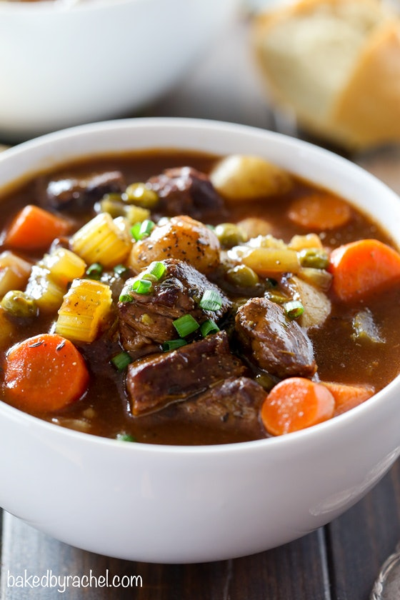 close up shot of white bowl full of beef stew with chunks of carrots and, potatoes, celery and beef